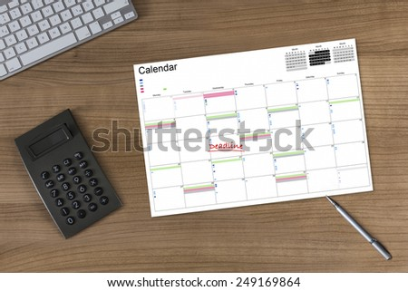 Calendar with the word Deadline on a wooden table with calculator modern keyboard and silver pen - stock photo
