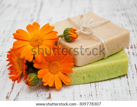 Calendula and handmade soap on a wooden background