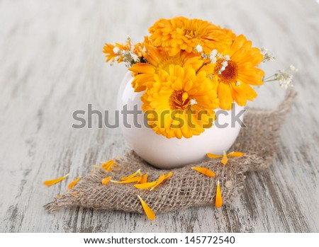 Calendula flowers in vase on wooden background - stock photo