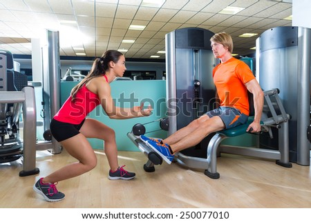 Calf extension man at gym exercise machine workout and personal trainer woman - stock photo