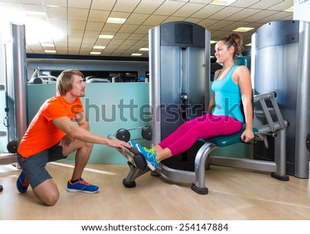 Calf extension woman at gym exercise machine workout and personal trainer woman - stock photo