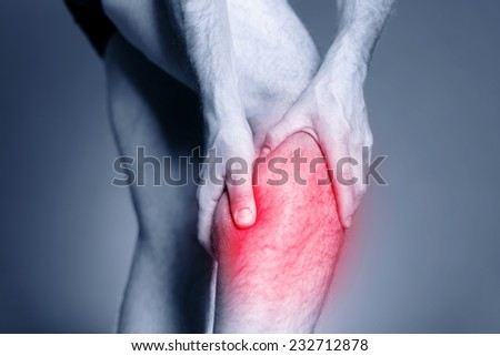 Calf leg pain, man holding sore and painful muscle, sprain or cramp ache filled with red pink bright place. Person injured when exercising or running - stock photo