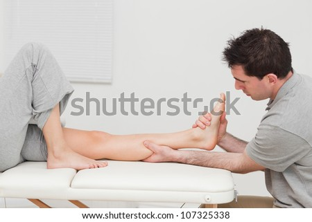 Calf of a patient being massaged by a physiotherapist in a room - stock photo