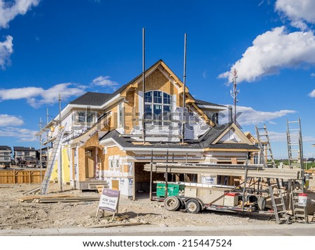 CALGARY, CANADA - AUG 31: Suburban estate home under construction in Aspen Woods on August 31, 2014 in Calgary, Alberta. This estate home is typical of upscale Calgary suburban districts. - stock photo