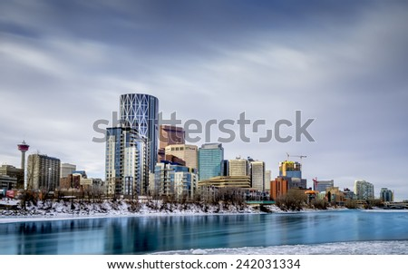 CALGARY, CANADA - Jan 1: Office towers on a cold winter day on January 1, 2015 in Calgary, Alberta Canada. The partially frozen Bow River is in the foreground. - stock photo