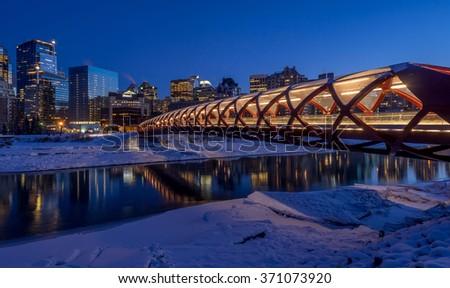 CALGARY, CANADA - JAN 23: the Peace Bridge on January 23, 2016 in Calgary, Alberta Canada. The pedestrian bridge spans the Bow River and was designed by Santiago Calatrava. Skyline in background. - stock photo