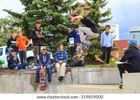CALGARY, CANADA - JUN 21, 2015: Athletes have a friendly skateboard competition in Calgary. California law requires anyone under the age of 18 to wear a helmet while riding a skateboard. - stock photo