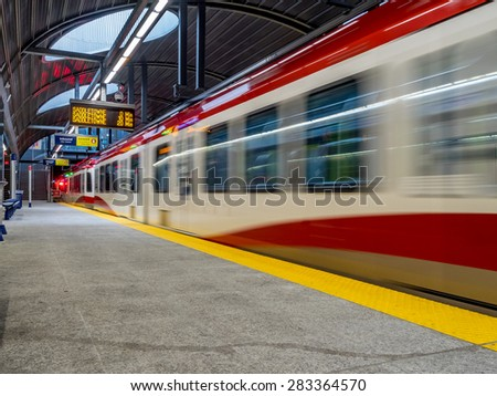 CALGARY, CANADA - MAY 24: The C-train speeding into Westbrook stations on  May 24, 2015 in Calgary, Alberta. The C-train is Calgary's light rail transit vehicle and moves over 300,000 people a day.