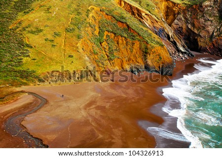 California coast landscape.  Aerial view of colorful cliffs, beach and ocean waves with lacy foam on the sand. A tiny person on the beach shows scale. Near San Francisco in beautiful Marin County.