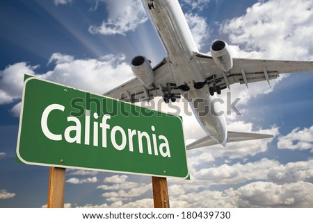California Green Road Sign and Airplane Above with Dramatic Blue Sky and Clouds. - stock photo