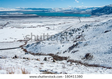 California Mountain Highway in Winter:  A scenic California highway crosses a snowy valley toward a distant lake in the Sierra Nevada Mountains near Yosemite National Park.  - stock photo