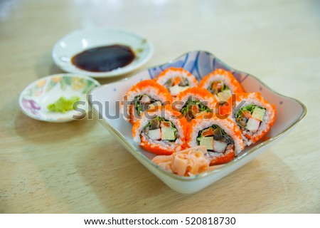 California roll Japanese food with side dish on wooden table at home