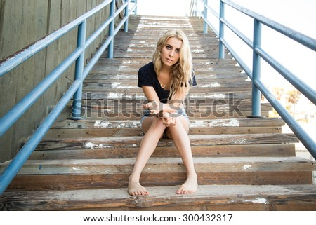 California surfer girl relaxes on stairs at the Santa Monica Pier on a summer day.