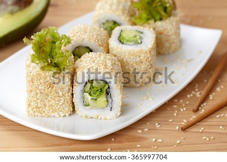 California vegetarian sushi roll with avocado, cucumber and salad. - stock photo