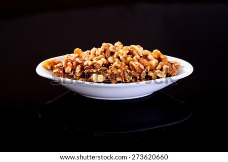 California Walnuts in a white plate on a black background