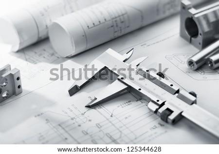 caliper and machine parts on mechanical blueprint - stock photo