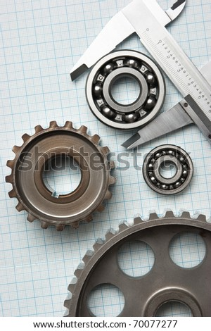 caliper with gears and bearings on graph paper - stock photo