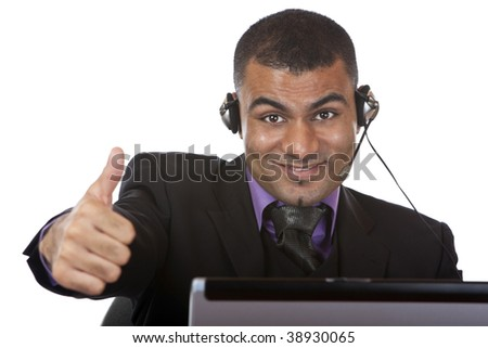 Call center agent wearing a headset and expressing happiness by showing thumb up. - stock photo