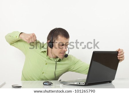 Call center agent with headset wants to hit the laptop. - stock photo