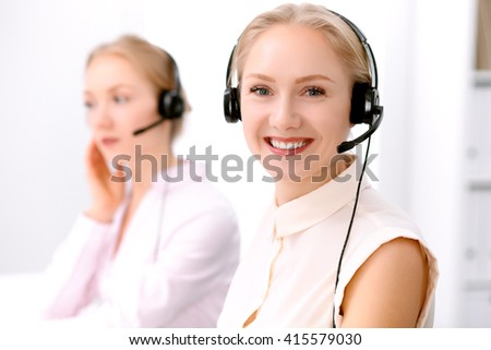Call center. Focus on beautiful blonde woman in headset - stock photo