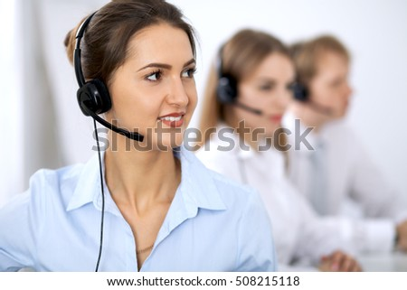 Call center operators. Focus on beautiful woman in headset