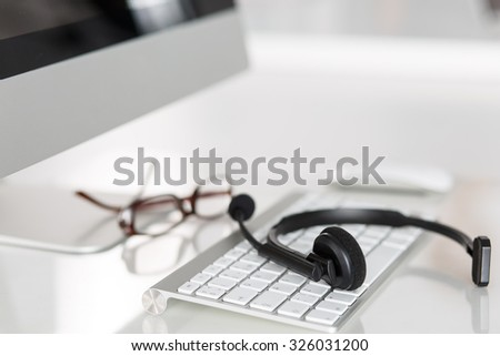 Call center service operator empty working place. Headset, glasses, keyboard and monitor at helpdesk employee workplace. Effective and efficient business information, help and support concept - stock photo