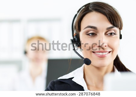 Call center service operators at work. Portrait of smiling pretty female helpdesk employee with headset at workplace. Effective and efficient business information, help and support concept - stock photo