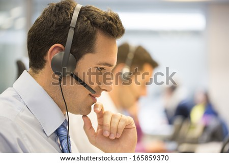 Call center team in the office on the phone with headset - stock photo