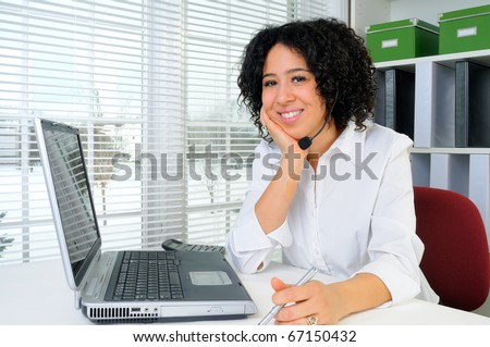 Call Center Woman Wearing A Telephone Headset At Her Desk In The Office - stock photo