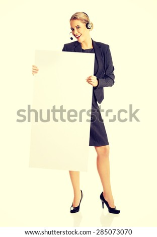 Call center woman with headset holding empty blank - stock photo