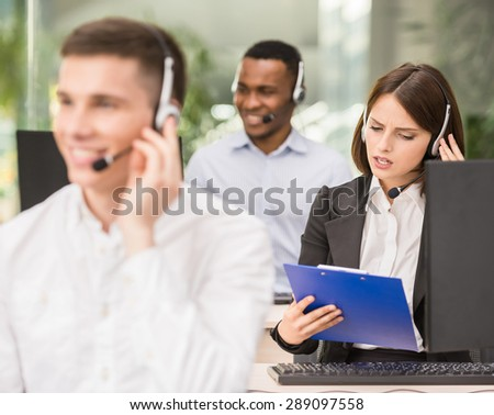 Call centre agents talking on the headset in the office. - stock photo