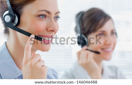 Call centre agents with headsets at work smiling  - stock photo