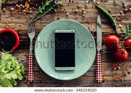 Call for delivery. Top view of plate and smart phone laying on the rustic wooden desk with vegetables around - stock photo