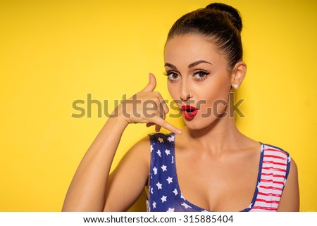 Call me, baby! Pretty young brunette woman showing phone sign with her fingers. Colorful studio portrait with yellow background. - stock photo