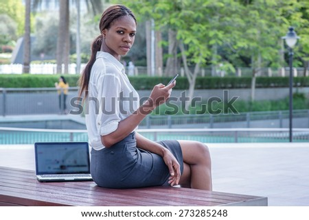 Call the customer's business. Confident businesswoman African businessman sitting in the street and holding cell phone in hand in Dubai downtown among the skyscrapers and looks forward - stock photo