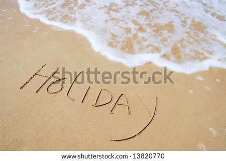 calligraphic type letters inscribed in sand by the sea waves