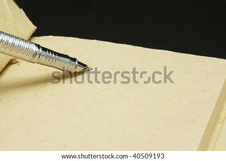 Calligraphy pen on ancient paper and black background - stock photo