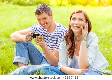 calling and surfing outdoor happy smiling couple - stock photo
