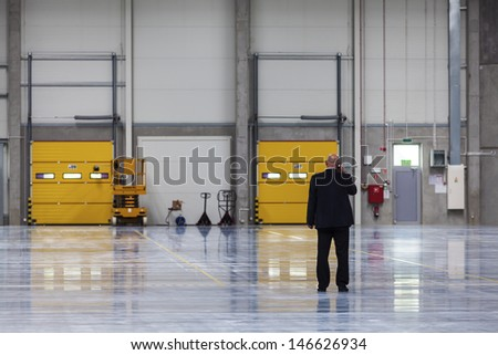 Calling businessman in modern storehouse - stock photo