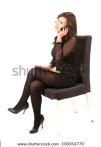 calling businesswoman with phone sitting on chair, full length, white background