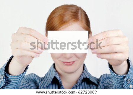 Calling card in female hands on a gray background - stock photo