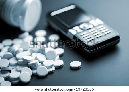 calling for medical help: white pills and mobile phone - stock photo