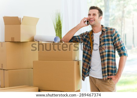 Calling from his new flat. Cheerful young man talking on the mobile phone while leaning at the cardboard box - stock photo