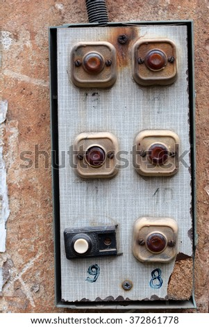 Calling on old wall with cracks. Intercom. Button on the wall. Background. Old wire on the wall. Facade. Paint.