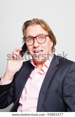 Calling young business man with blond hair in blue suit and pink shirt sitting on chair in office. Wearing glasses. Holding cellphone.