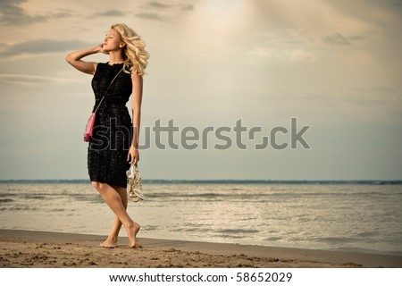 Calm and barefoot. A pretty blonde in a black dress standing barefoot on the beach. - stock photo