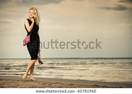 Calm and barefoot. Fashionable young woman in dress with handbag paddling on sandy beach.