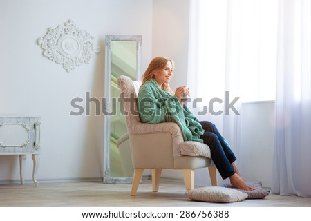 Calm and coziness. Attractive young woman with cup of coffee sitting on armchair at home. Light beautiful interior.