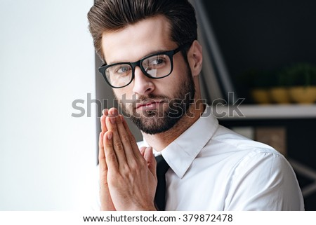 Calm and handsome. Handsome young businessman in glasses looking away and keeping hands clasped while standing in office  - stock photo