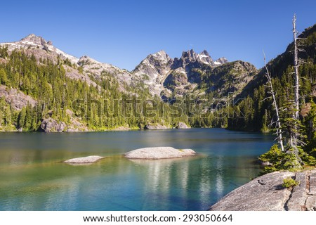 Calm and relaxing landscape of clear and tranquil water with rugged mountain peak - stock photo